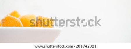Crystallized ginger root  in white porcelain bowl. Bowl is cut vertically. Shallow DOF. Close-up photo, banner - stock photo