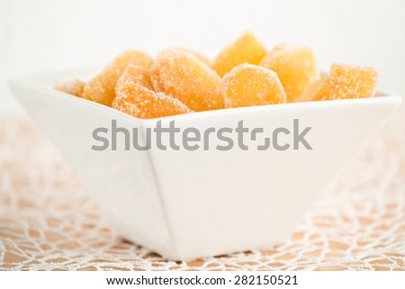 Crystallized ginger root  in white porcelain bowl. Bowl is cut vertically. Shallow DOF. Close-up photo, horizontal - stock photo