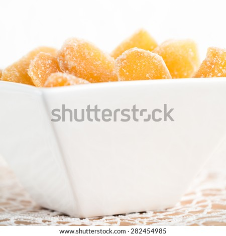 Crystallized ginger root  in white porcelain bowl. Bowl is cut vertically. Shallow DOF. Close-up photo, square