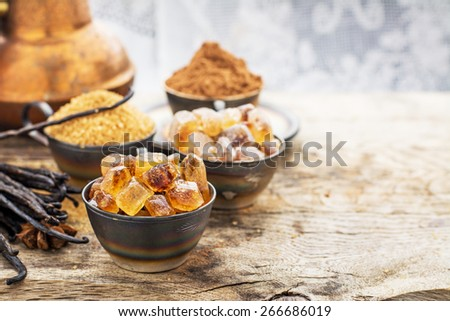 Crystals caramel brown sugar, natural vanilla pods, star anise, sugar cane, cocoa powder in old metal cup on a wooden background. selective Focus - stock photo