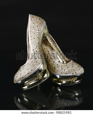 crystals encrusted golden shoes on black background - stock photo