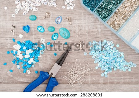 Crystals, pendants, charms, plier, glass hearts, box with beads and accessories to create hand made jewelry on old wooden background. Top view - stock photo