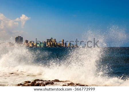 Cuba. Island. Ocean. Sea. Waves breaking on the shore. White spray soar high. Storm. Freedom. Blue water. Nature. City. high buildings.   - stock photo