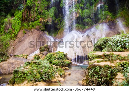 Cuba. Island. Waterfall in the mountains. Greenery. Trees, bushes. Blue and white water. Spray. Jungle. Leaves. Sticks. Stone. Liana. Lake. Nature