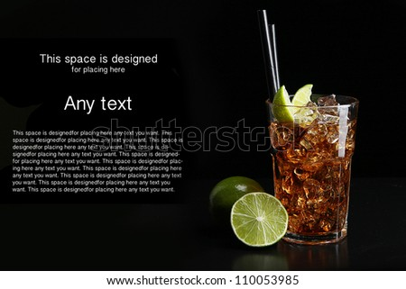 Cuba Libre cocktail, black background, ice and lime - stock photo