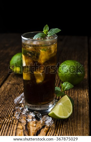 Cuba Libre longdrink with pieces of fresh lime and crushed ice on wooden background - stock photo