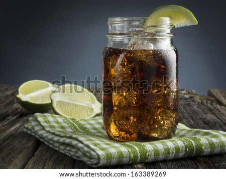 Cuba Libre or rum and cola drink with ice and lime in mason jar - stock photo