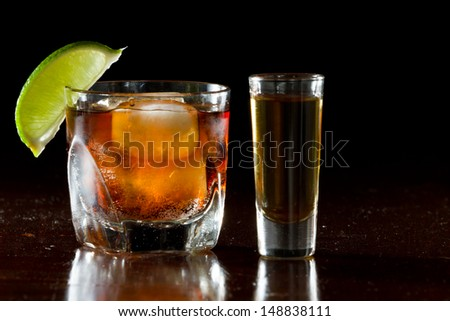 cuba libre, rum and cola cocktail served in a short glass with a lime garnish and a shot of rum on the side - stock photo