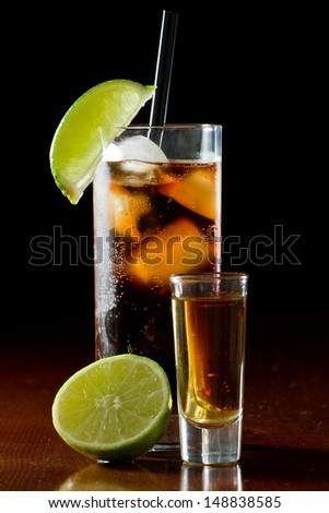 cuba libre, rum and cola cocktail served in a tall glass with a lime garnish and a shot of rum on the side - stock photo