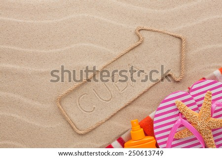 Cuba  pointer and beach accessories lying on the sand, as background - stock photo