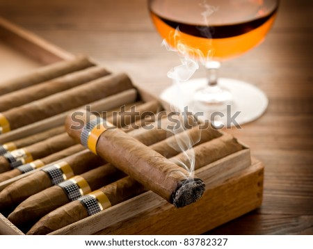 cuban cigar and glass of  liquor on wood background - stock photo