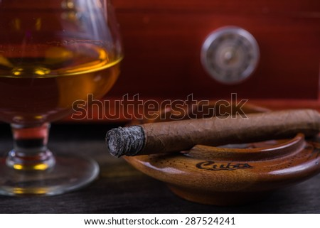 Cuban cigar,humidor and rum on wooden rustic table