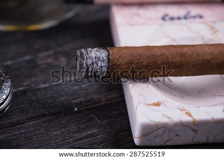 Cuban cigar in expensive marble ashtray on rustic table - stock photo