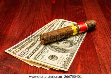 Cuban cigar on a several dollar bills on the table