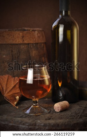 cuban cigars and cognac in glass, bottles and barrel on a wooden background - stock photo