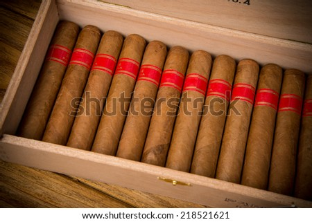 Cuban cigars and humidor on rustic wooden table - stock photo