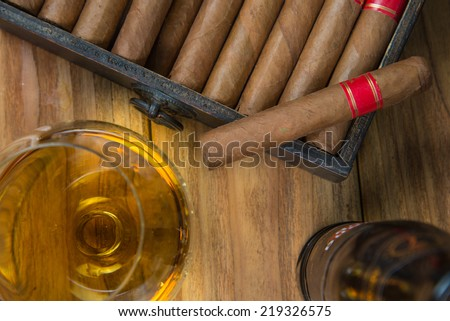 Cuban cigars and Rum or other alcohol in glass on table top view with vintage wooden background - stock photo