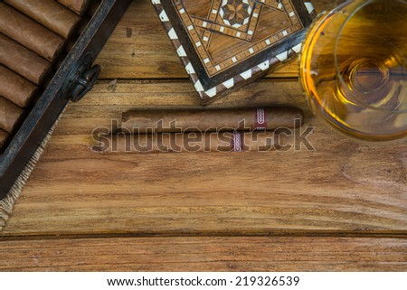 Cuban cigars and Rum or other alcohol in glass on table top view with vintage wooden background and copy space - stock photo