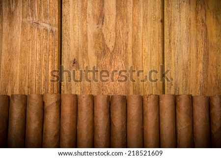 Cuban cigars on rustic wooden table in line on the edge of background - stock photo