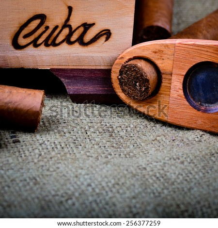 Cuban cigars with cutter on a hessian background. - stock photo