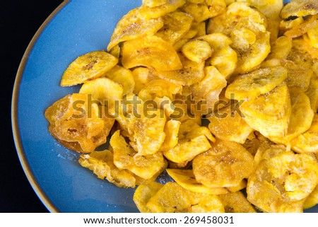 Cuban Cuisine: delicious green plantain salty chips or fries served for snack in a blue plate. Green plantain chips or fries are part of the Cuban traditional and creole cuisine - stock photo