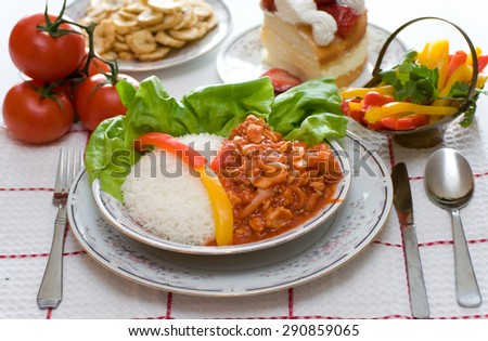 Cuban cuisine: Fish in tomato sauce.Meal consisting of rice, fish in tomato sauce, and vegetables, with sliced bananas and cake for dessert, perfect as lunch or dinner. - stock photo