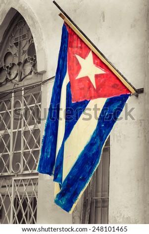 Cuban flag on a grunge decaying neighborhood in Havana - stock photo