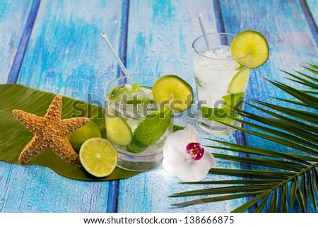 Cuban Mojito cocktail in tropical blue wood with flowers and starfish - stock photo