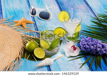 Cuban Mojito cocktail in tropical blue wood with sunglasses flowers and starfish - stock photo
