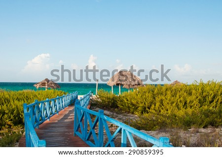 Cuban Santa Maria Beach: Wooden trail with handrails leads to the beach between the green plants on the exotic coast - stock photo