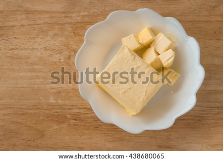 cube butter in white plate on wooden board ,butter is unhealthy you should not eat too much - stock photo