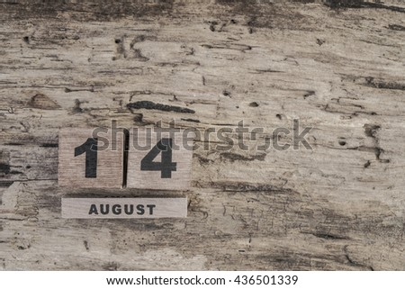 cube calendar for august on wooden background with copy space