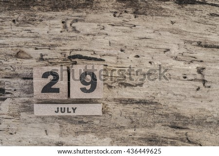 cube calendar for july on wooden background with copy space