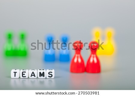 Cube Letters show teams  in front of unsharp ludo figures. Background is light gray - stock photo