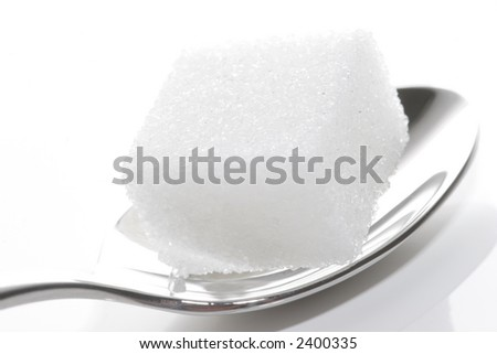 cube of white sugar on spoon