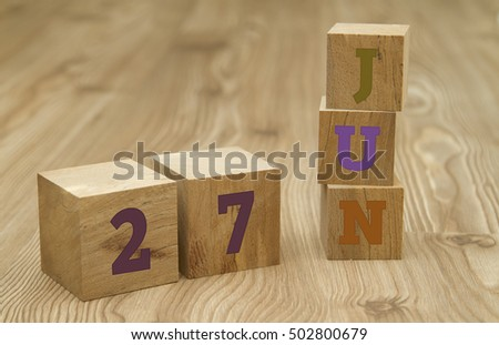 Cube shape calendar for June 27 on wooden surface.