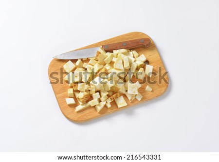 cubed celery and kitchen knife on wooden cutting board - stock photo