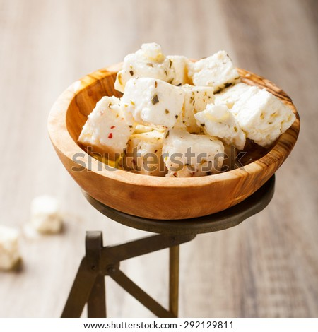 Cubed feta cheese in olive wood bowl on old rustic scales. Selective focus. - stock photo
