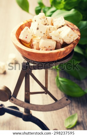 Cubed feta cheese in olive wood bowl on old rustic scales with basil. Selective focus. Retro style toned. - stock photo