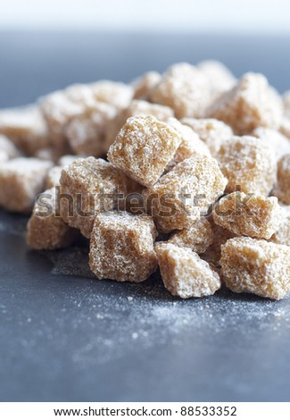 Cubes of brown whole cane sugar on black background, small depth of field - stock photo