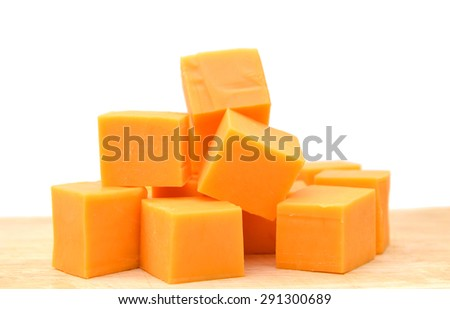Cubes of Colby Cheese isolated on wooden board