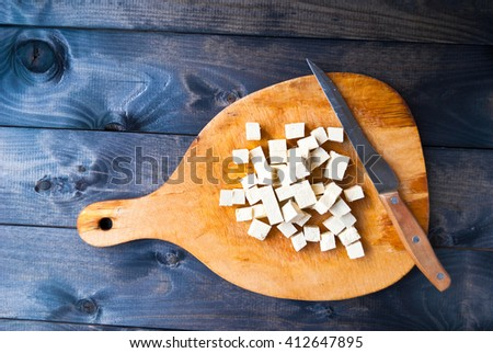 Cubes of raw tofu, fresh spinach and knife on shabby cutting board - stock photo