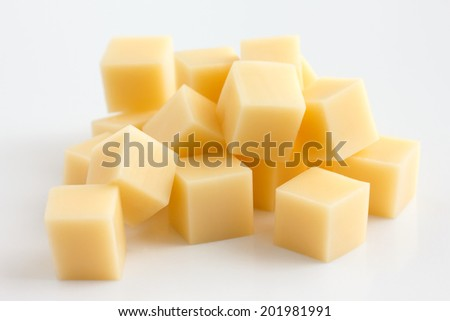 Cubes of yellow cheese stacked randomly on white. - stock photo