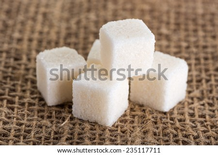 cubes white and sugar on a background of jute bags - stock photo