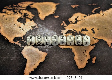 Cubes with text, POLITICS, on world map - stock photo