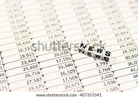 Cubes with the text, NEWS, on spreadsheet - stock photo