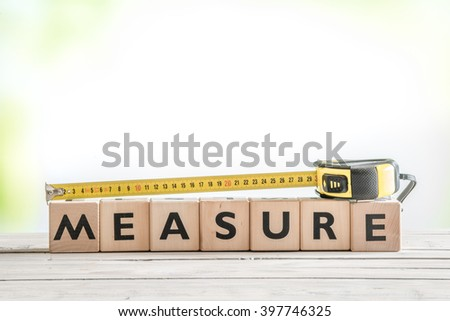 Cubes with the word measure on a table - stock photo