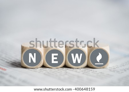 "cubes with the word ""new"" on a newspaper - stock photo"