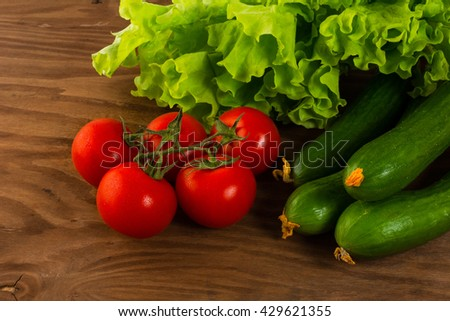Cucumber and cherry tomato on wooden background. Tomato.  Cucumber.  Ripe vegetables. Fresh vegetables. Cherry tomato. Healthy eating. Vegetables. - stock photo