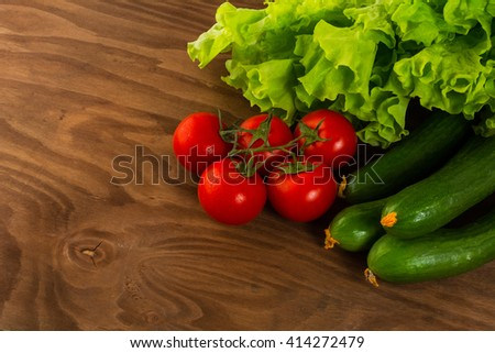 Cucumber and cherry tomato on wooden table Tomato.  Cucumber.  Ripe vegetables. Fresh vegetables. Cherry tomato. Healthy eating. Vegetables. - stock photo